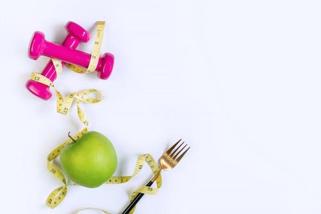青リンゴ、ダンベル、白いテーブル背景に巻尺