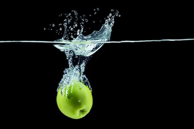 Зеленое яблоко падает в воду с всплеском на темном фоне