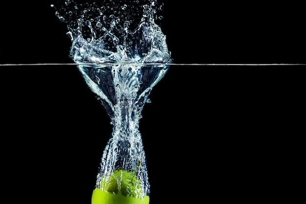 Зеленое яблоко падает в воду с всплеском на темной стене крупным планом