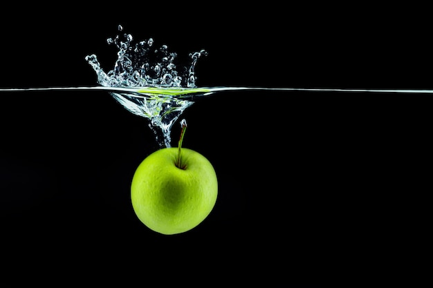 Green apple falling in water with a splash against dark  close up