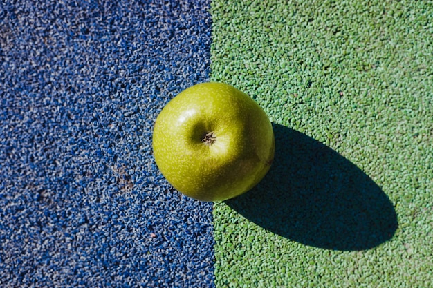Green apple, on the ground divided into two colors, seen from above.