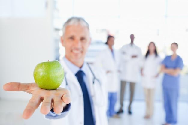 緑色のリンゴは、彼の後ろのチームと医者によって開催