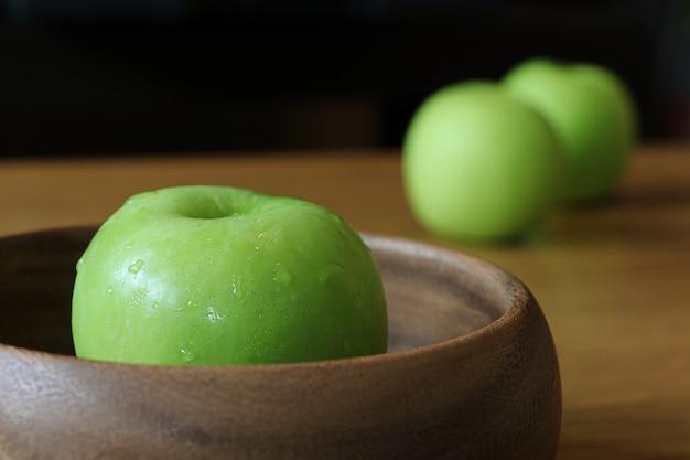 オーク材のテーブルの上の木製のボウルに青リンゴ