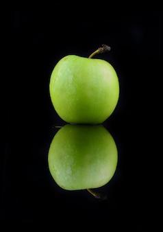 黒の背景に分離された青リンゴ