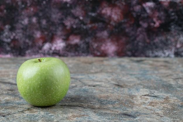 Зеленое яблоко, изолированные на бетоне.