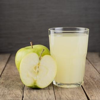 木製のテーブルの上にフルーツとグラスの青リンゴジュース。