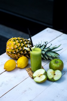 Green apple juice served with apple, pineapple and lemons on white wood table