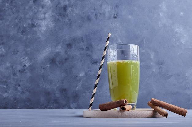 Green apple juice on a wooden platter.