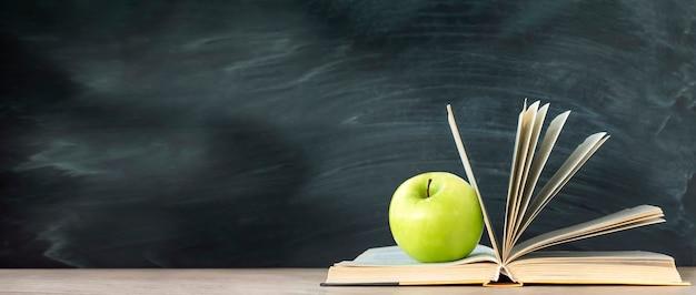 Зеленое яблоко лежит на книге. классная доска