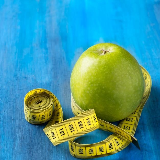 Green apple and measure tap. closeup