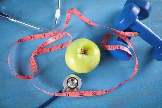 녹색 사과, 측정 테이프, 아령, 파란색 배경에 청진기.