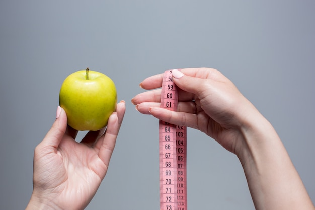 Green apple and measuring tape in female hands on gray wall