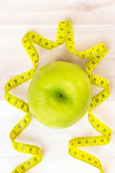 Green apple, measuring tape on a light wooden surface. preparation for the summer season and the beach, weight loss and sports concept. vertical photo