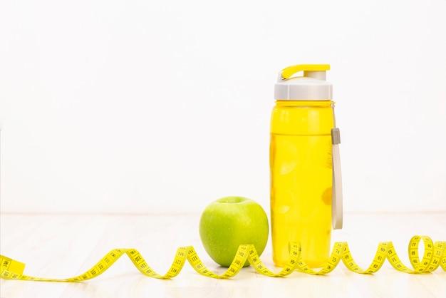 Зеленое яблоко, измерительная лента, бутылка воды на светлом фоне деревянные. потеря веса и спортивная концепция