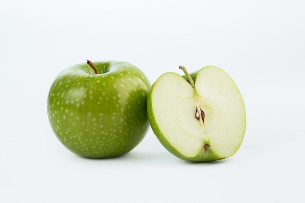 Fresco succoso dolce della mela verde isolato sul pavimento bianco