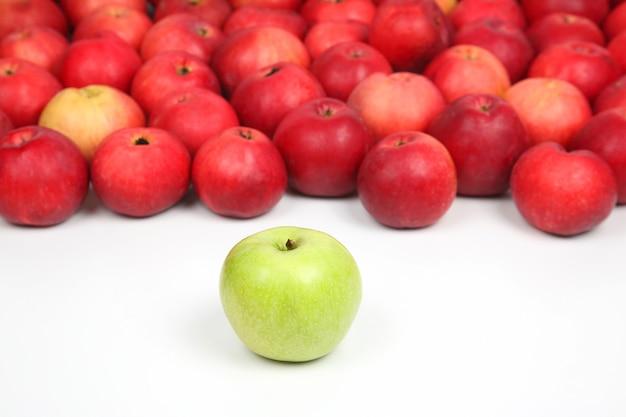 Зеленое яблоко на фоне красных яблок