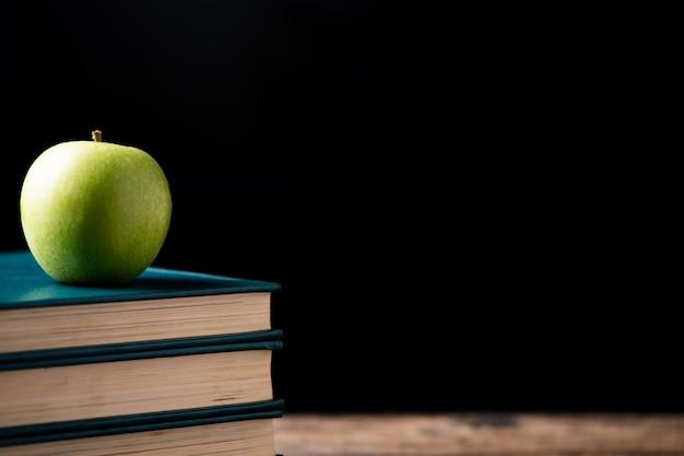 学校のセンターへの本の青リンゴ。学校に戻るコンセプト