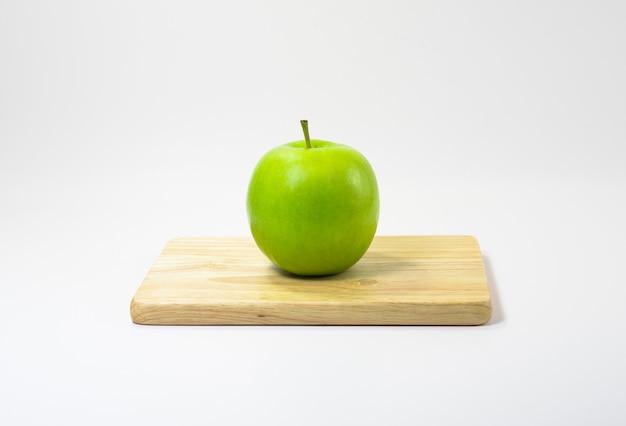 白い背景のまな板に青リンゴ。