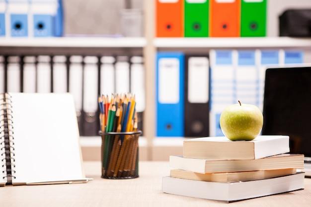 ノートブックの横にある本の山に青リンゴ、後ろにぼやけたホワイトボードが付いたテーブルに鉛筆。学校のコンセプト