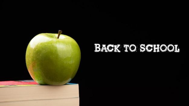 Green apple on stacks books on desk for back to schoolconcept