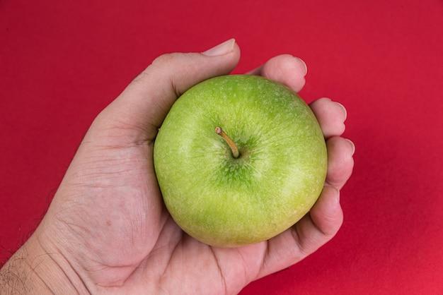 赤い背景の上の青リンゴ-保持している男