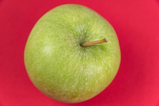 赤い背景に青リンゴ 無料写真