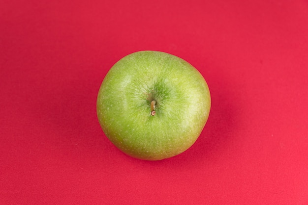 Зеленое яблоко на красном фоне