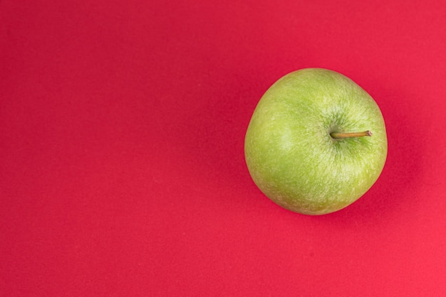 Зеленое яблоко на красном