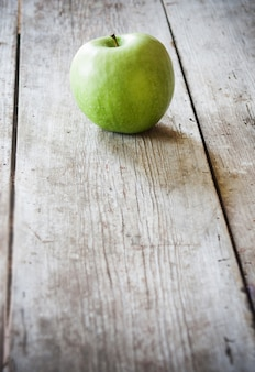 木製のテーブルの上の青リンゴ