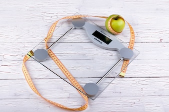 Green apple, orange  tape-measure lie on glass weighing scales