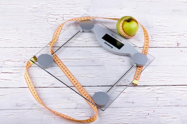 Зеленое яблоко, оранжевая рулетка лежат на стеклянных весовых весах