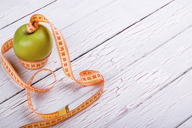 Green apple and orange tape-measure lie on white wooden floor