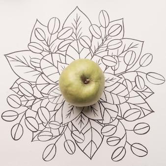 Зеленое яблоко на фоне цветочного контура