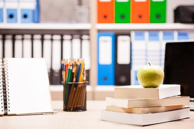 Green apple on pile of books next to a notebook and pencils on table with a blurred white board in the back. school concept