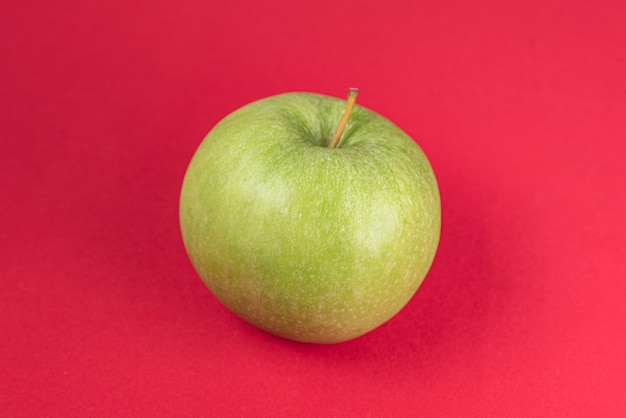 Green apple on the red