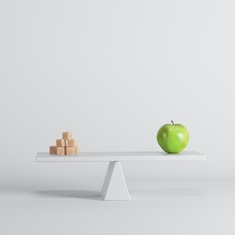 Green apple seesaw with sugars on opposite end on white background.