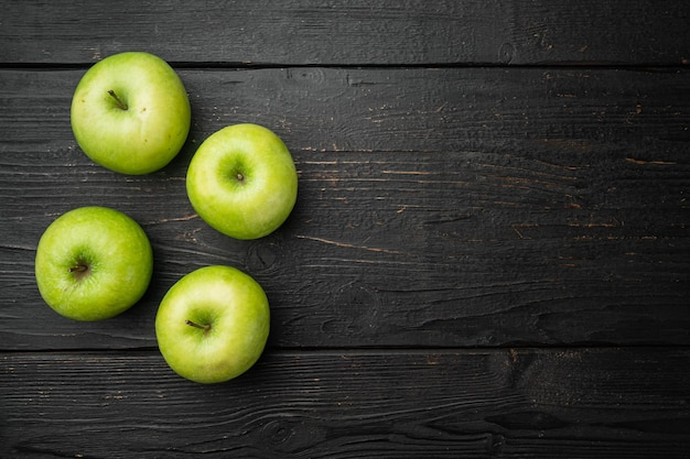 Набор зеленых яблок, на черном фоне деревянного стола, плоская планировка, вид сверху, с копией пространства для текста
