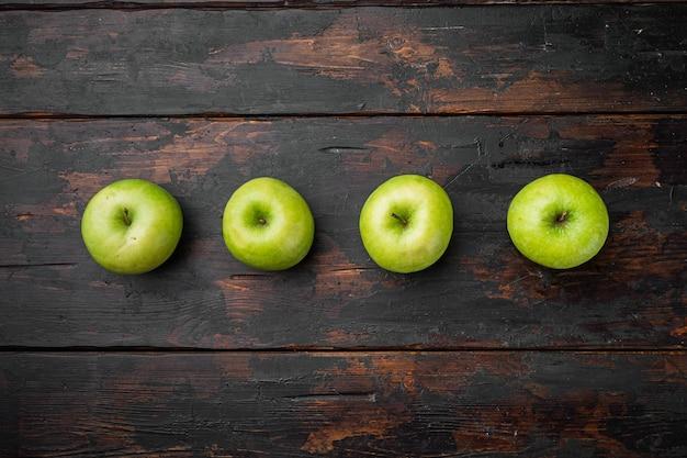 Набор зеленых яблок, на старом темном деревенском фоне стола, плоская планировка, вид сверху, с копией пространства для текста