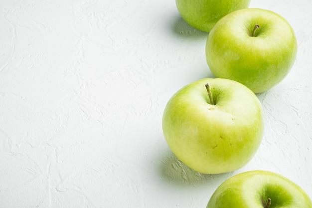 흰색 돌 테이블 배경에 녹색 사과 세트, 텍스트 복사 공간