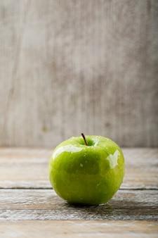 Vista laterale della mela verde sul lerciume e sul fondo di legno leggero