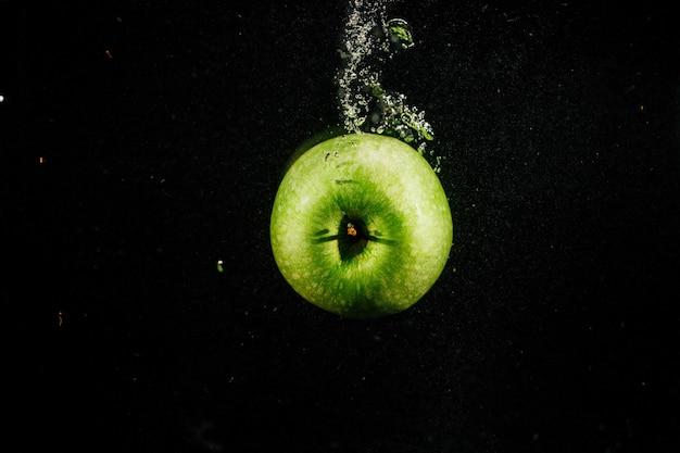 Green apple splashes water falling on black background