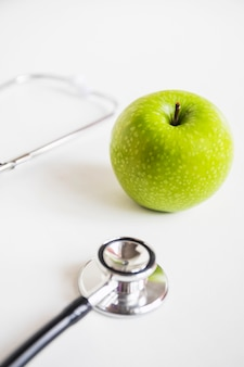 Green apple and stethoscope on white background