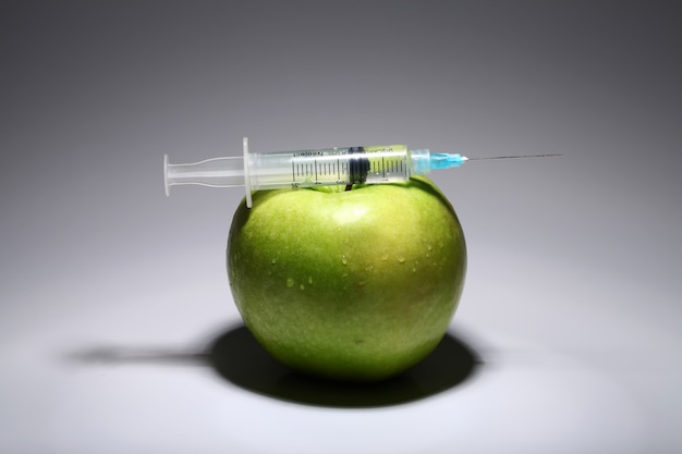 Green apple and syringe