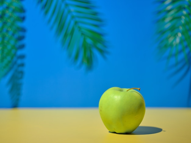 Green apple on the table on a natural background