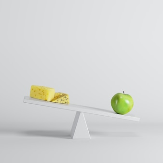 Green apple tipping seesaw with cheese on opposite end on white background.