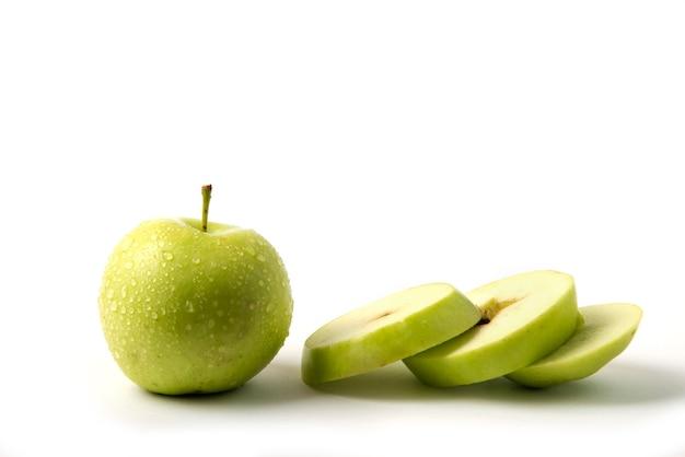Зеленое яблоко целиком и нарезано на белом
