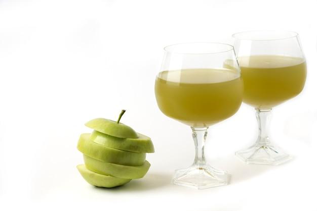 Mela verde intera e affettata su bianco con un bicchiere di succo