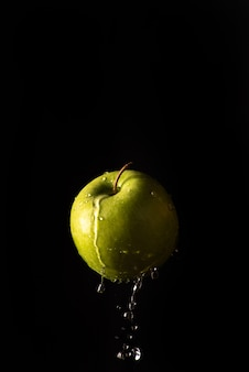 Green apple with beautiful splash of water with black background and selective focus.