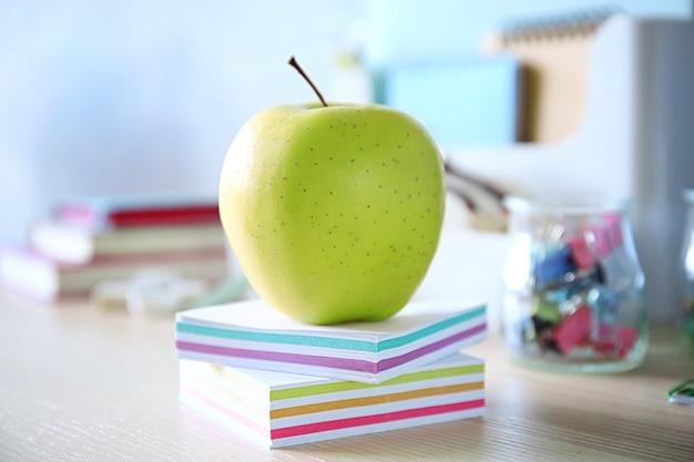 Зеленое яблоко с красочными канцелярскими принадлежностями
