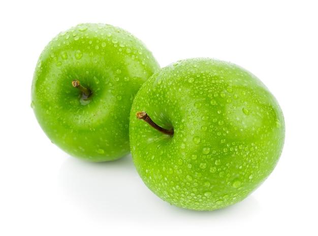 Зеленое яблоко с каплей воды на белой поверхности